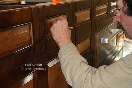 Earl marking pull placements on custom made cabinets